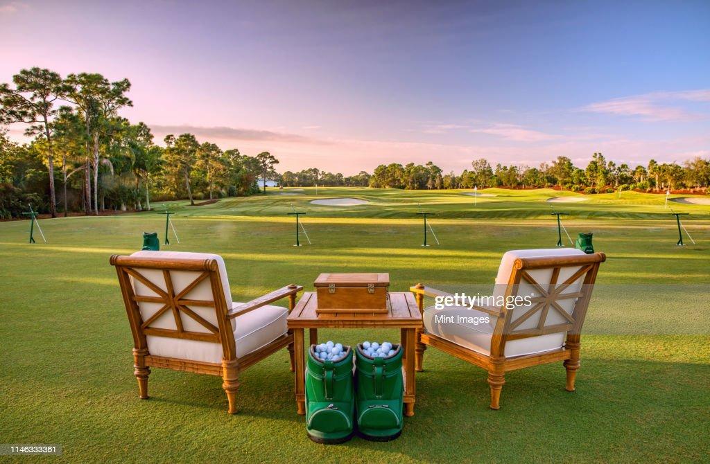 Chairs and golf balls on driving range : ストックフォト