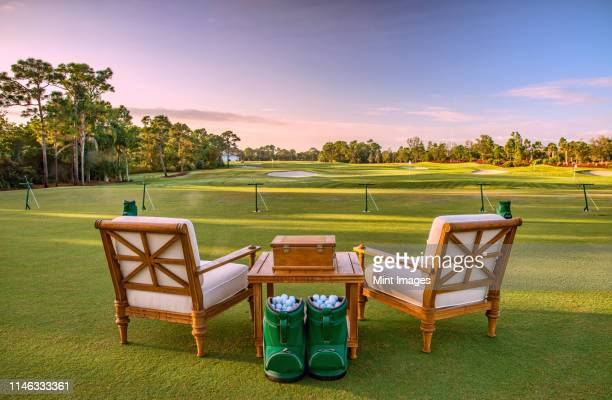 chairs and golf balls on driving range - southeast stock pictures, royalty-free photos & images