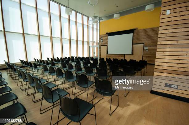 chairs and projection screen in empty room - auditorium stock pictures, royalty-free photos & images