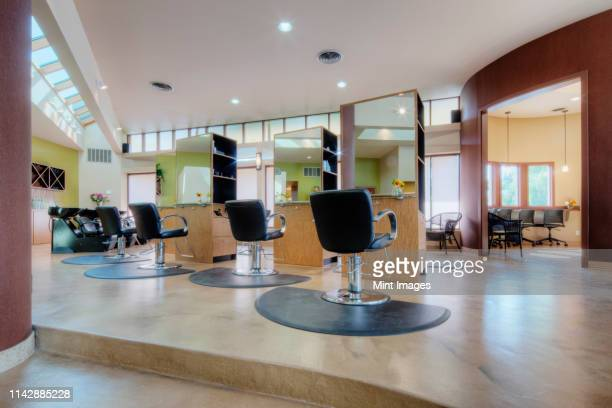 chairs and stations in empty beauty salon - tidy room stock pictures, royalty-free photos & images