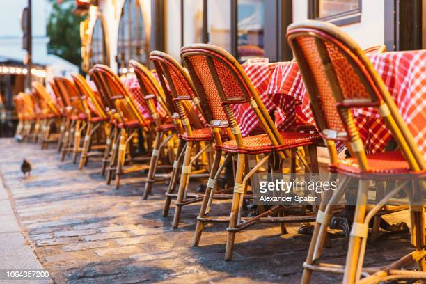 chairs and table at typical sidewalk cafe in paris, france - cultura francesa fotografías e imágenes de stock