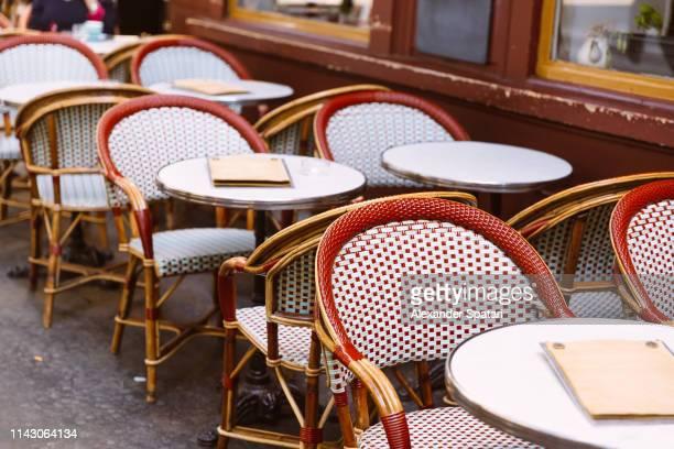 chairs and table in a traditional parisian sidewalk cafe - terrasse de café photos et images de collection