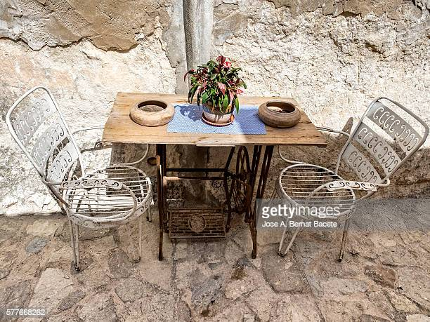 Chairs and table of garden done with an ancient sewing machine in the street, in an ancient people