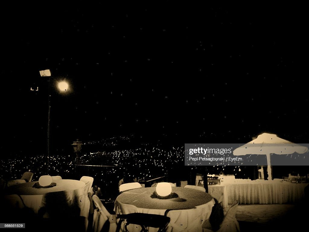 Chairs And Tables Arranged Illuminated City At Night : Stock Photo