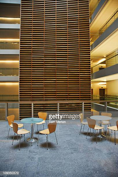 chairs and tables in modern office building cafe - building atrium stock pictures, royalty-free photos & images