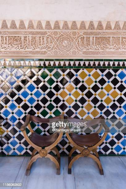 chairs and tiles wall in the alhambra - ancient stock pictures, royalty-free photos & images