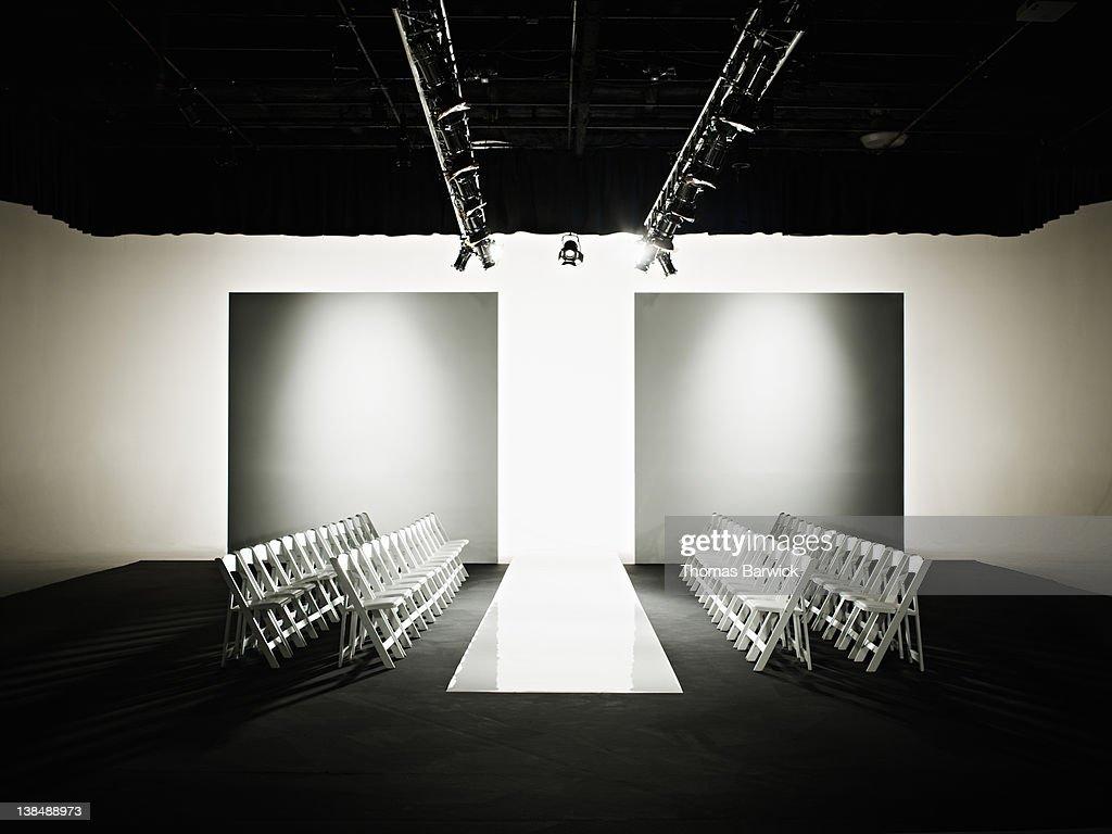 Chairs around catwalk set for fashion show : Bildbanksbilder