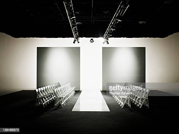 chairs around catwalk set for fashion show - fashion runway stock pictures, royalty-free photos & images