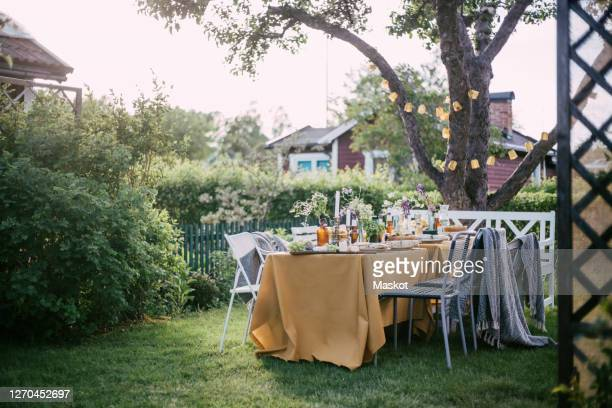 chairs arranged by table at backyard during garden party - garden party stock pictures, royalty-free photos & images
