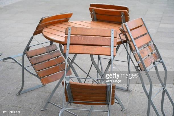 chairs collected from a closed bar terrace during coronavirus time. berlin. germany. - stänga bildbanksfoton och bilder