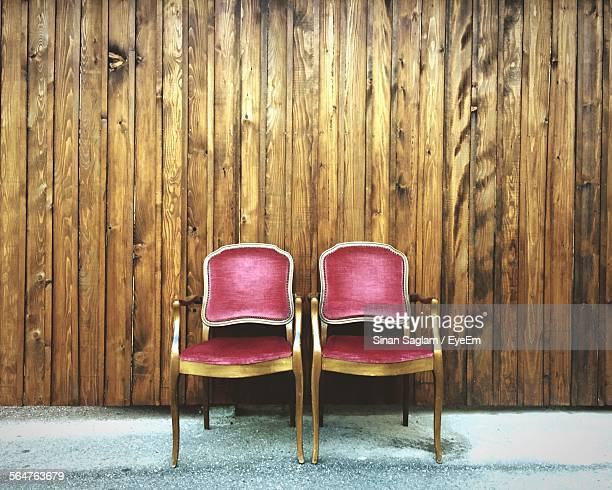 chairs in front of wooden wall panel - two objects stock photos and pictures