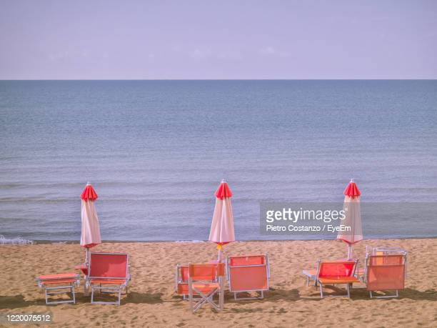 chairs on beach by sea against sky - pastore maremmano foto e immagini stock