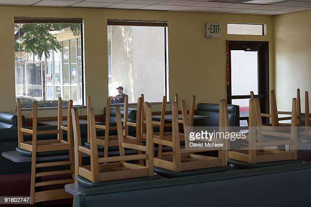 Chairs remain on dining tables inside a drivethrough fast food restaurant in a strip mall after its tenants had been evicted on October 8 2009 in...