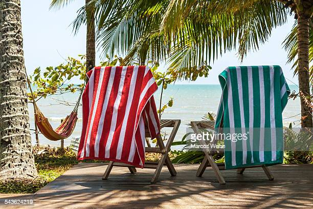 Chairs with beach towels on deck by the beach