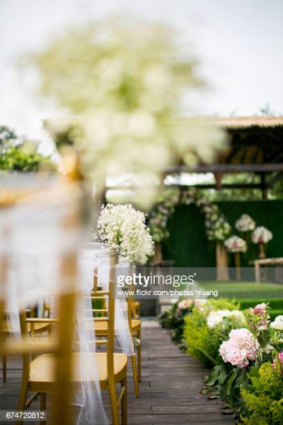 Chairs with floral decoration beside grassy aisle