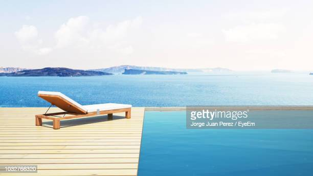 chaise longue by sea against sky - chaise longue stock photos and pictures