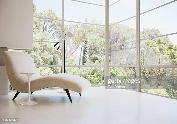 Chaise lounge chair near windows