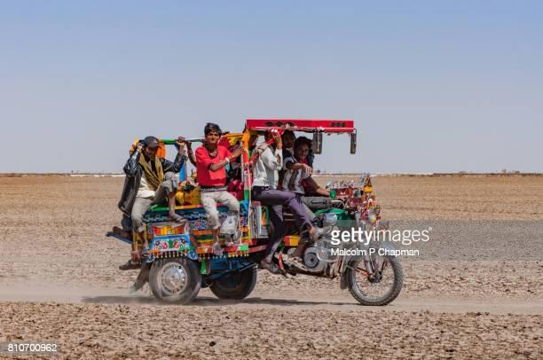 Chakda motorcycle rickshaw filled with salt workers on the Little Rann of Kutch, salt pans near Dhrangaghra, Gujarat, India