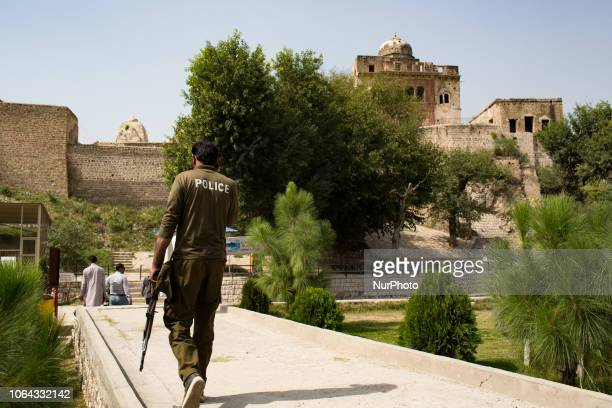Chakwal, Pakistan, 1 October 2018. A policeman guard a temple in the Katas Raj Temples site. The Hindu temples form a complex surrounding a pond...