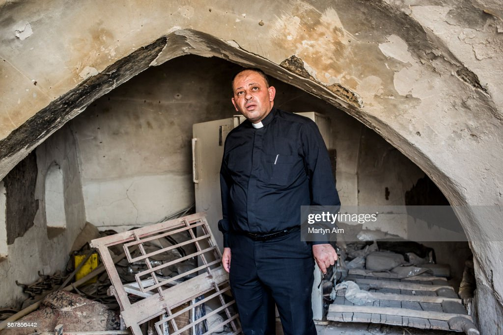 Chaldean Catholic Father Thadet inside his family home - damaged and burned by Islamic State militants - in Karamles, a Christian town in northern Iraq, on September 8, 2017.