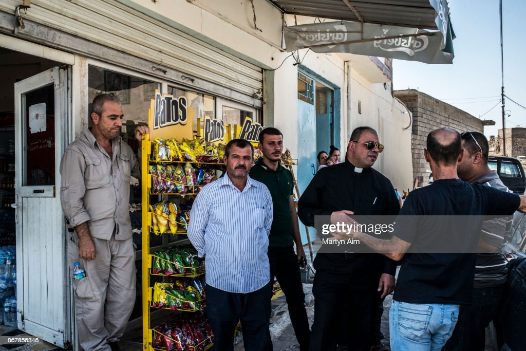 Chaldean Catholic Father Thadet talks with locals outside a reopened store in Karamles, a Christian town in northern Iraq, on September 8, 2017.
