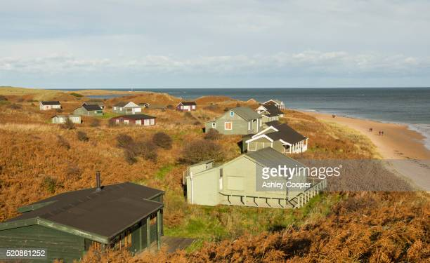 chalets built in the sand dunes at low newton by the sea on northumberlands coast, uk. - holiday villa stock pictures, royalty-free photos & images