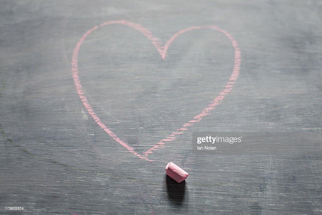 Chalk and heart shape on blackboard : Stock Photo