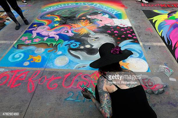 Chalk artist Nixi Pixi works on her creation called Epic Battle of Mythical Creatures during the Denver Chalk art festival on Larimer Square in...