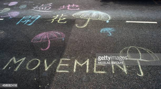 """Chalk drawing of umbrellas and the word """"Movement"""" is seen on the ground at the pro-democracy protesters camp site in the Admiralty district of Hong..."""