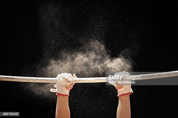 Chalk dust flies from the hands of a Canadian athlete after landing a manoeuvre on the high bar during a practice session ahead of the 2015 World...