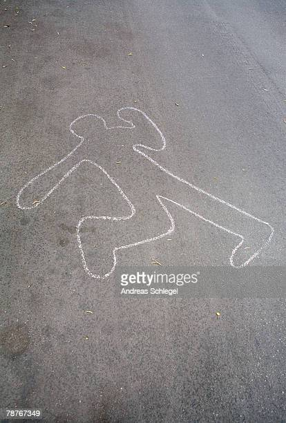 A chalk outline of a body on the road