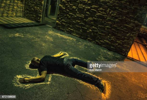 Chalk outline of body of Caucasian victim on pavement