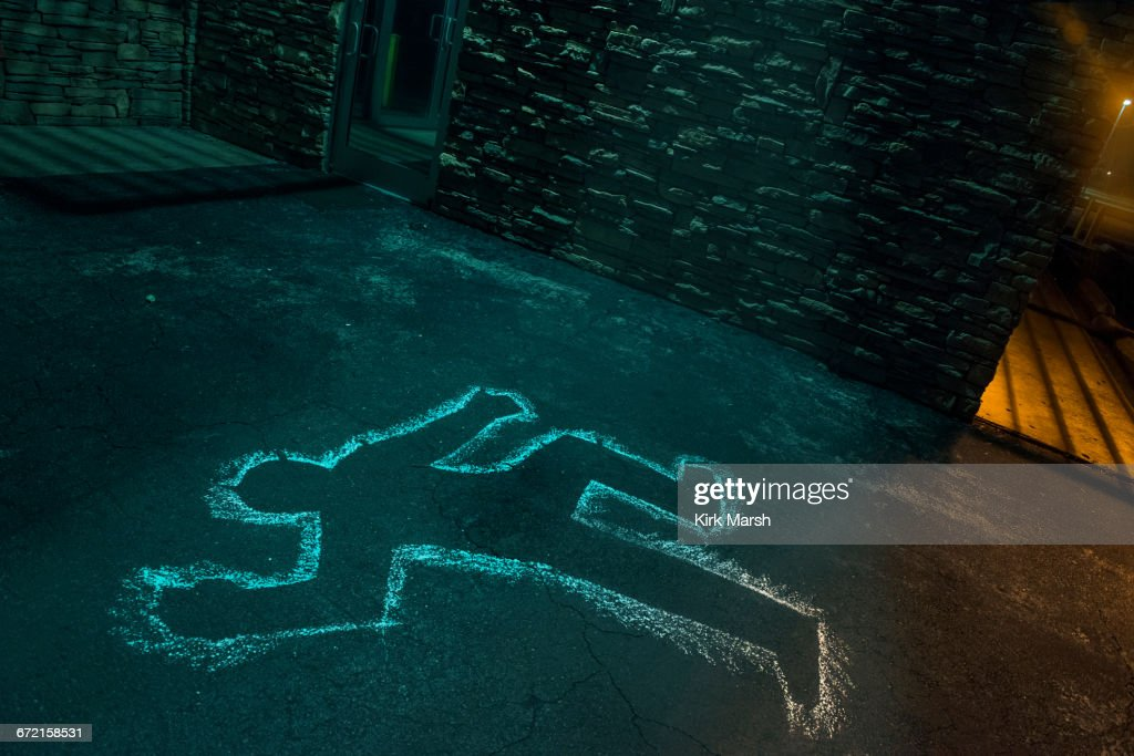 Chalk outline of body of victim on pavement : Stock Photo