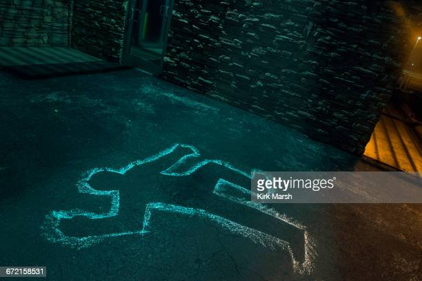 chalk outline of body of victim on pavement - dead body stockfoto's en -beelden