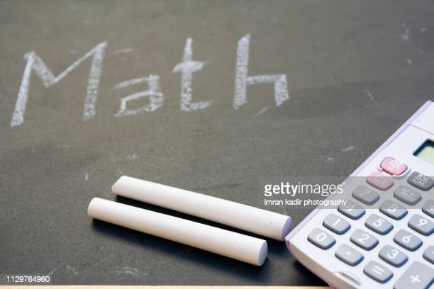 Chalkboard and digital calculator. with math texted on board.