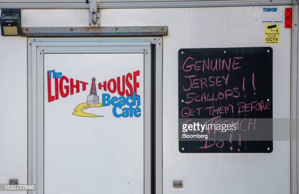 """Chalkboard sign at a seafood stall reads """"Genuine Jersey Scallops!! Get them before the French do!!"""" in Le Mare, Jersey, on Saturday, May 8, 2021...."""