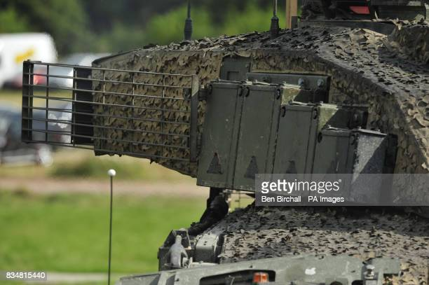 A Challenger 2 tank with extra armour fitted in the form of heavy duty metal grids causing antitank weapons to detonate further from the body of the...
