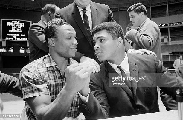 Challenger Cleveland Williams and titleholder Cassius Clay compare their big guns after signing to battle for the world heavyweight championship in...