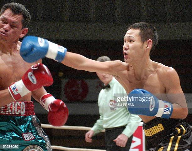Challenger Katsunari Takayama of Japan throws a right straight onto boxing champion Isaac Bustos of Mexico during the WBC strawweight title match in...