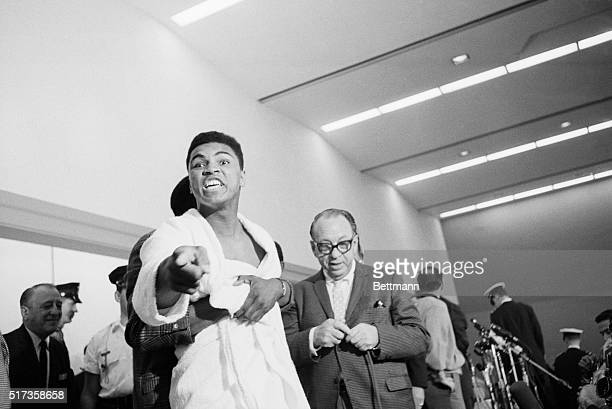 Challenger Muhammad Ali, when he was known as Cassuis Clay, strains to break away from a friend who held him as he tried to lunge at champion Sonny...