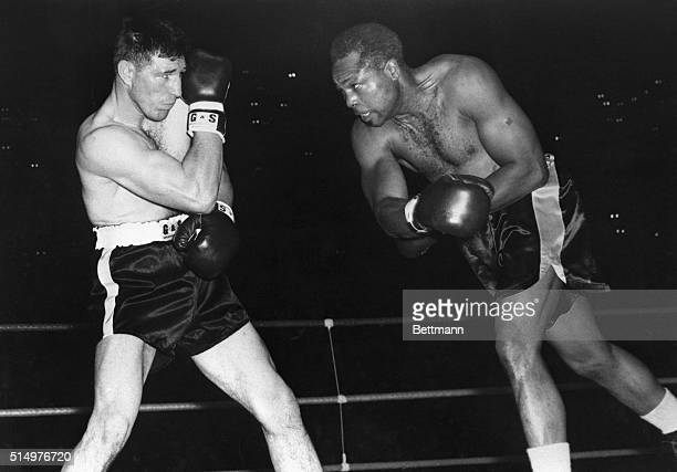 Challenger Yvon Durelle rocks back to avoid a vicious right swung by World LightHeavyweight Champion Archie Moore in round one of their fight in the...