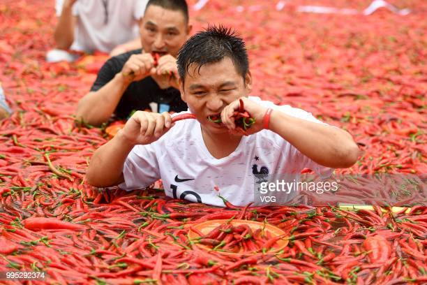 Challengers standing in a chilicovered pool eat chilies during a chilieating contest on July 8 2018 in Ningxiang Hunan Province of China Citizen Tang...