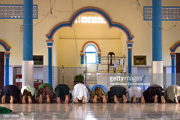 Cham muslim men kneeling during the afternoon prayer, in a small local mosque on the countryside of Kompong Cham, Cambodia .