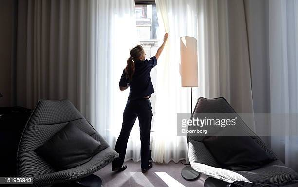 A chambermaid draws the curtains in a bedroom at DD London Ltd's South Place hotel in London UK on Thursday Sept 13 2012 London hotels' average room...