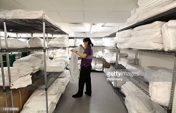 Chambermaid folds bedding sheets in a laundry room at a Premier Inn hotel at Heathrow airport in London, U.K., on Friday, April 20, 2012. Whitbread...