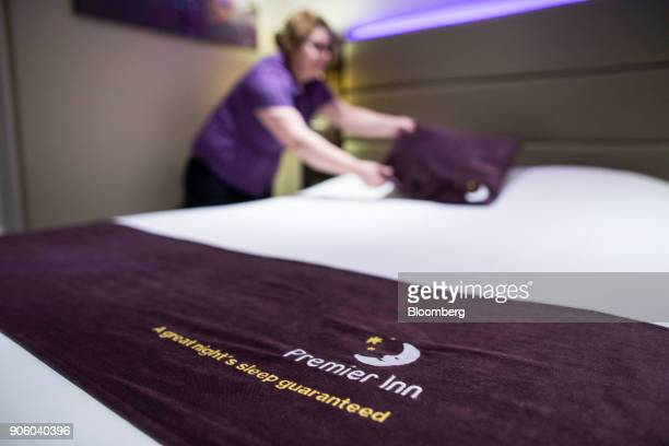 A chambermaid makes a bed in a bedroom at a Premier Inn hotel operated by Whitbread Plc in London UK on Wednesday Jan 17 2018 The hotel and...