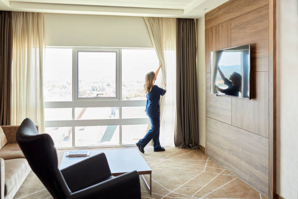 Chambermaid opening curtains of window in hotel bedroom