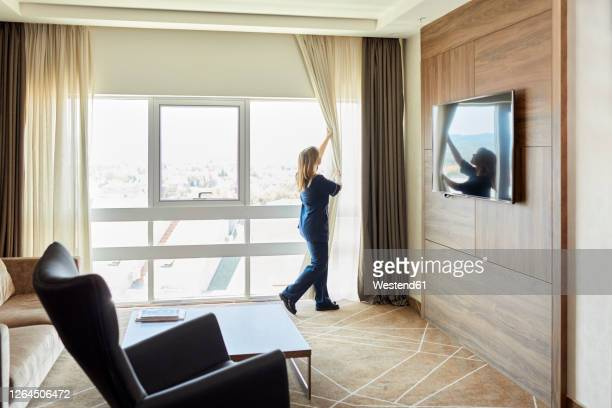 chambermaid opening curtains of window in hotel bedroom - housework stock pictures, royalty-free photos & images