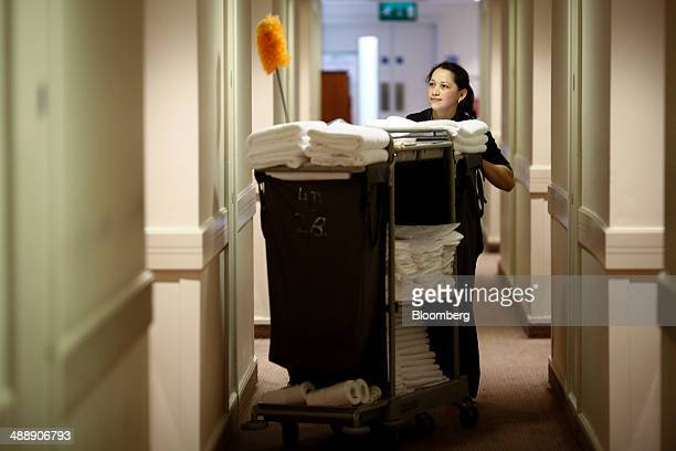A chambermaid pushes a cleaning trolley along a room corridor in this arranged photograph taken inside a Holiday Inn hotel operated by...