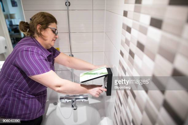 A chambermaid replaces a soap dispenser in an ensuite bathroom at a Premier Inn hotel operated by Whitbread Plc in London UK on Wednesday Jan 17 2018...